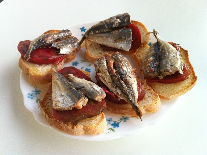 An example of some dishes in the tapas route in Barcelona: sardinas with tomatoes