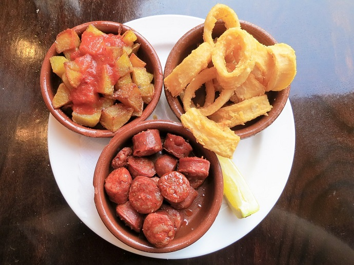 An example of some dishes in the tapas route in Barcelona: chorizos, patatas bravas and calamares